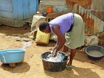 年轻非洲妇女洗涤的衣裳都市乌干达 库存照片