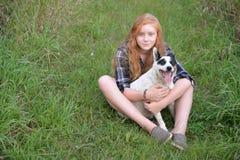 非离子活性剂女孩长的头发红色头和狗 免版税库存图片
