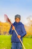 非洲微笑的男孩在公园拿着红色犁耙 库存图片