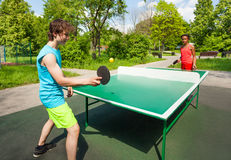 非洲打乒乓球的女孩和男孩外面 库存图片