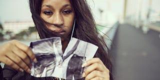 非洲浓缩妇女悲伤听的音乐撕毁的照片的终止 免版税库存照片