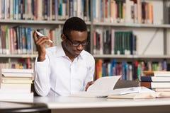 非洲男学生在图书馆里 免版税库存照片