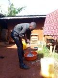 非洲男孩洗涤的衣裳 库存图片
