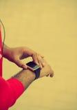 非洲男性的手使用巧妙的手表的 图库摄影