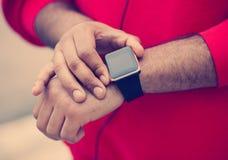 非洲男性的手使用时髦巧妙的手表的 免版税库存照片