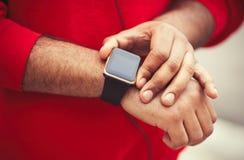 非洲男性的手使用时髦巧妙的手表的 库存图片