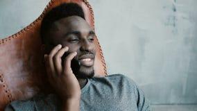 年轻非洲男性画象坐在椅子和谈话在智能手机 供以人员笑和点头他顶头同意 免版税图库摄影