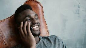 年轻非洲男性画象坐在椅子和谈话在智能手机 供以人员笑和点头他顶头同意 库存图片