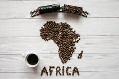非洲的地图放置在与咖啡的白色木织地不很细背景的由烤咖啡豆制成,玩具火车 库存图片