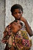 非洲矮小的逗人喜爱的女孩运载的小兄弟 免版税库存图片