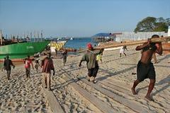 非洲装卸工人卸载在桑给巴尔, Tanza港的木材船  图库摄影