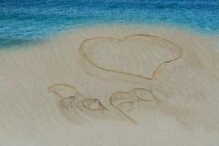 靠岸与一拉长在沙子心脏和词爸爸里 免版税库存照片