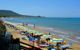 靠岸与伞和未认出的人民在拥挤海滩在fortore附近出海口  库存图片