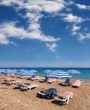 靠岸与伞和椅子在太阳和蓝天下 免版税库存图片
