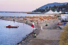 靠岸与伞在日落在圣雷莫,意大利 免版税库存照片