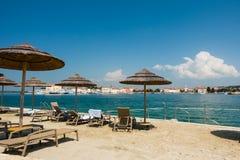 靠岸与在早晨光的海滩睡椅在海滩 库存照片