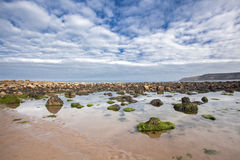 靠岸与在沙子的岩石在Cayton海湾,英国 免版税库存图片