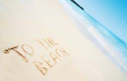 靠岸与手书面文本到海滩和海 库存图片