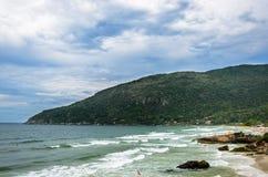 靠岸与有些岩石和一座山在背景 免版税库存照片