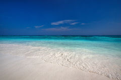 靠岸与清楚的水和白色美好的沙子 免版税库存图片