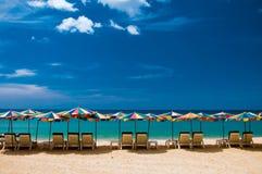 靠岸与白色沙子、椅子和umbrrellas 蓝色覆盖天空白色 免版税库存照片