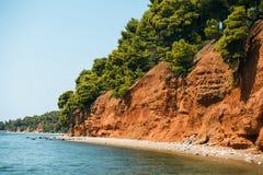 靠岸与红色土地和绿色杉木在Metamorfosi,希腊 库存照片