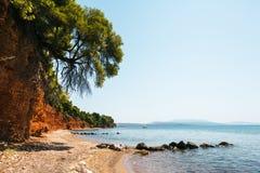 靠岸与红色土地和绿色杉木在Metamorfosi,希腊 图库摄影