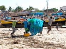 靠岸与马达加斯加人的独木舟和渔夫有捕鱼网的,马达加斯加 免版税库存图片