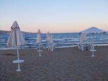靠岸在与海滩睡椅和伞的微明下 库存图片