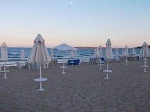 靠岸在与海滩睡椅和伞的微明下 库存照片