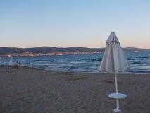 靠岸在与海滩睡椅和伞的微明下 免版税库存图片