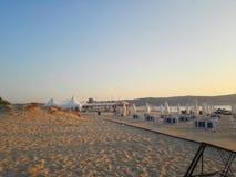 靠岸在与海滩睡椅和伞的日出 库存图片