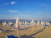 靠岸在与海滩睡椅和伞的日出 免版税库存图片