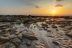 靠岸在金黄日落光在显示沙子格式的低潮期间 库存照片