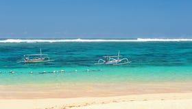 靠岸在巴厘岛有海视图和有海岸线的两条小船在与小云彩的一个晴天在的天际 库存照片