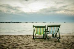 靠岸,两张轻便折叠躺椅和蓝天 免版税库存照片