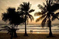 靠岸,平衡日落,走在海滩的人夫妇  免版税库存照片