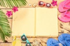 靠岸,棕榈树离开,空白的书、沙子、太阳镜和触发器 免版税库存图片