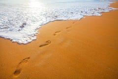 靠岸,波浪和脚印在日落时间 库存照片