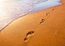 靠岸,波浪和脚印在日落时间 免版税库存图片
