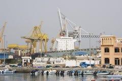 靠码头的Khor Fakkan阿拉伯联合酋长国大货船在Khor Fakkport装载和卸载物品 库存图片