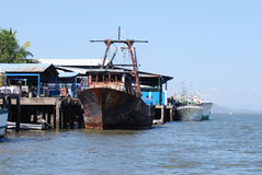 靠码头钓鱼旧港口生锈的船 库存照片