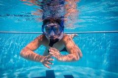 面具下潜的男孩在游泳池 库存照片