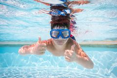 面具下潜的男孩在游泳池 免版税库存照片