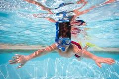 面具下潜的男孩在游泳池 免版税图库摄影