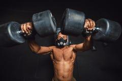 面具举的哑铃的非裔美国人的运动人和从上面研究他的胸口意图 做锻炼的健身房的黑人 免版税库存图片