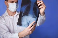 面具的和白色外套藏品X-射线或者伦肺,fluorography,在蓝色背景的图象男性医生 免版税库存图片