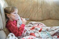 面具的小女孩,使用雾化器的咳嗽治疗在家 免版税库存照片