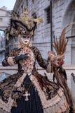面具的惊人的妇女,穿戴在黑色和金服装,运载的鸟笼,站立与叹气桥梁后边在Th期间 图库摄影