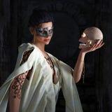 面具的美丽的性感的巫婆与头骨 库存照片